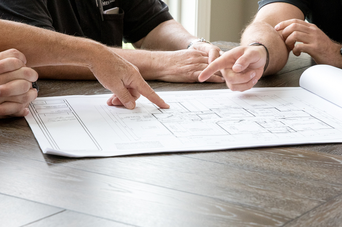 2 people pointing to building plans